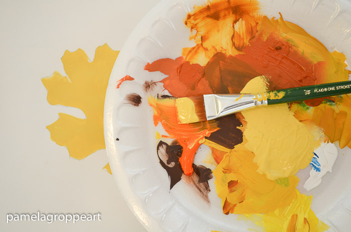 yellow and orange paint on paint brush